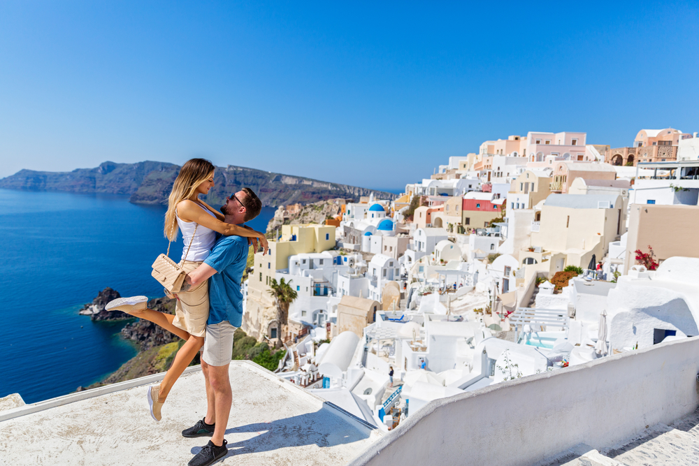 Couple on cliff-side of Santorini, Greece