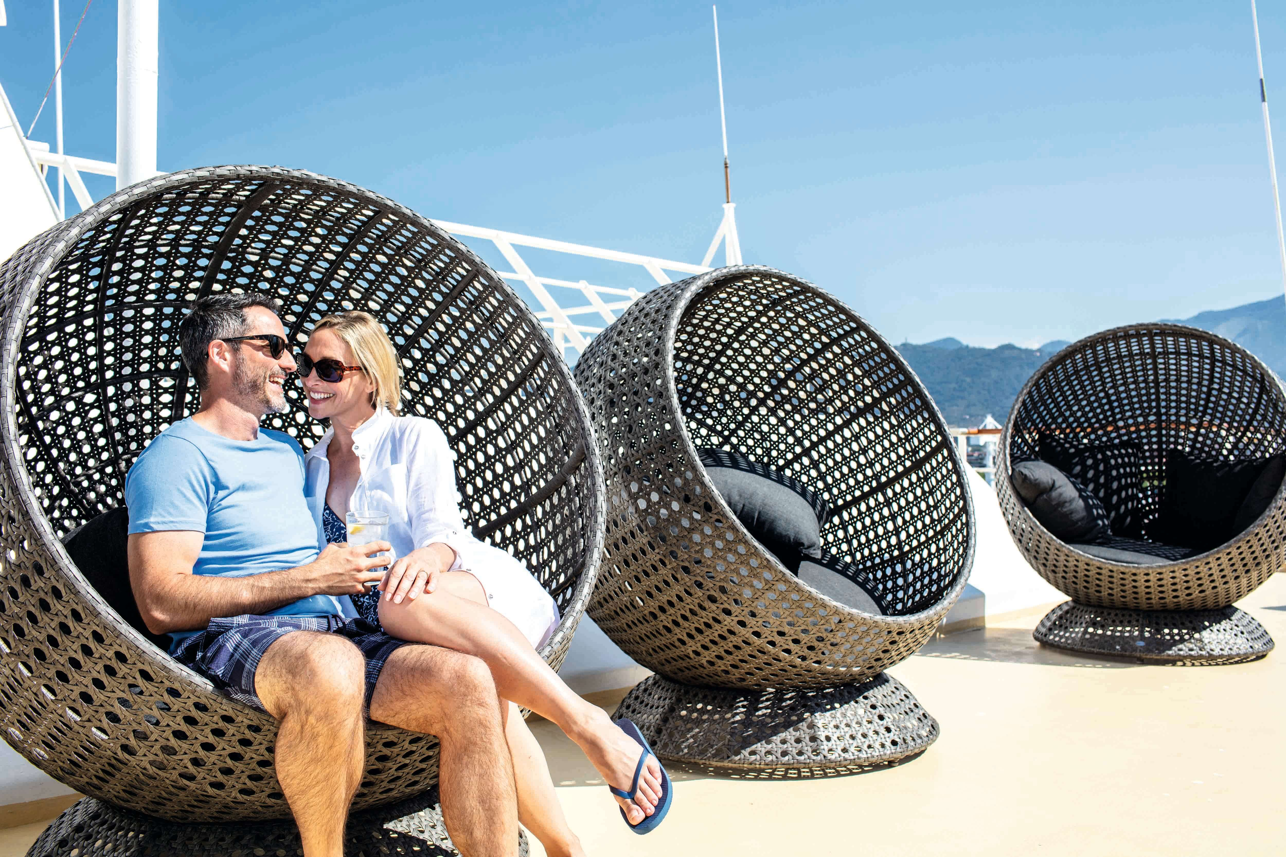 An image of a couple sat laughing on a funky chair on Deck 14, in the space known as The Veranda