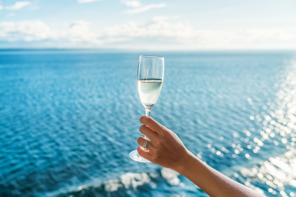 Image of Champagne glass woman's hand toasting on ocean background at luxury cruise ship during sunset