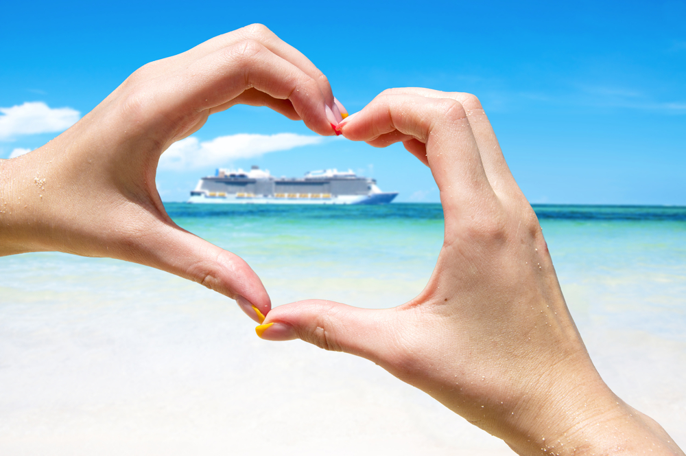 Hands shaped as a love heart around cruise ship